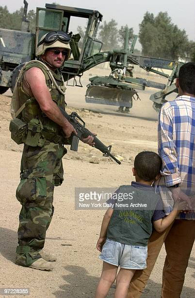 An Iraqi man and boy look past Navy Seabee John Shirmer who stands guard as a grader levels land for a children's soccer field in the southern port...