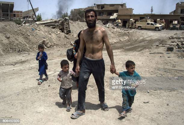 An Iraqi man and children flee the Old City of Mosul on July 3 during the government forces' ongoing offensive to retake the city from Islamic State...