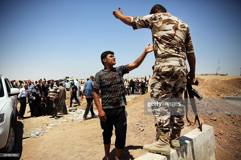 An Iraqi man argues with a Kurdish soldier as Iraqis who have fled recent fighting in the cities of Mosul and Tal Afar try to enter a temporary displacement camp but are blocked by Kurdish soldiers on July 2, 2014 in Khazair, Iraq. The families, many with small and sick children, have no shelter and little water and food. The displacement camp Khazair is now home to an estimated 1,500 internally displaced persons (IDP's) with the number rising daily. Tens of thousands of people have fled Iraq's second largest city of Mosul after it was overrun by ISIS (Islamic State of Iraq and Syria) militants. Many have been temporarily housed at various IDP camps around the region including the area close to Erbil, as they hope to enter the safety of the nearby Kurdish region.