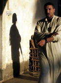 An Iraqi man being temporarily detained by troops from the US Army 10th Calvalry 1st Brigade 4th Infantry Division walks past the shadow of a soldier...