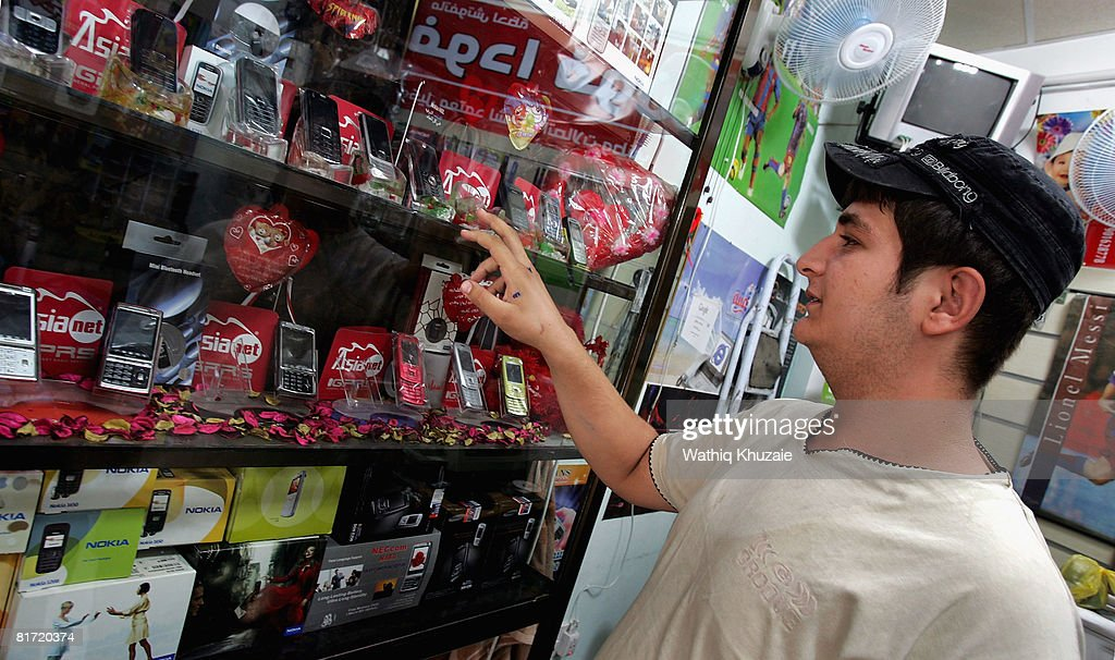 An Iraqi man buys a mobile phone at a store on June 26, 2008 in Baghdad, Iraq. The war-damaged aging landline telephone infrastructure means Iraqis are increasingly more dependent on mobile phones in daily life and business.