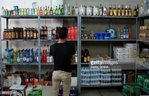 An Iraqi man buys alcohol at a shop in the embattled city Mosul on May 10 2017 Alcohol never completely disappeared from the city which for more than...