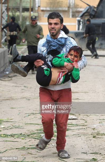 TOPSHOT An Iraqi man carries a young boy who was injured by a mortar shell fired by Islamic State group jihadists on civilians who were gathered to...