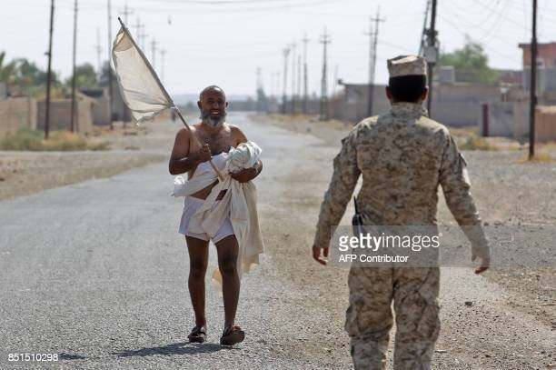 TOPSHOT An Iraqi man carries his clothes as he heads towards Iraqi forces after they entered the northern Iraqi town of Sharqat on September 22...