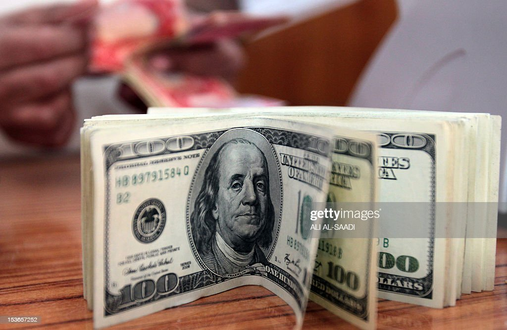 An Iraqi man counts money behind a pile of American dollars in his currency exchange bureau in Baghdad on April 11, 2012, as the price of goods went up across the country due to the new inflated exchange rate of the US dollar. AFP PHOTO / ALI AL-SAADI