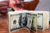 An Iraqi man counts money behind a pile of American dollars in his currency exchange bureau in Baghdad on April 11 as the price of goods went up...