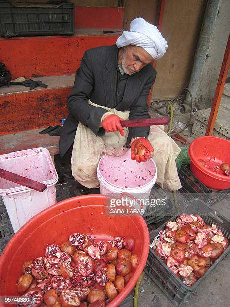 An Iraqi man cracks pomegranates to be used for juicing on January 13 at a stall in Baghdad The pomegranates which are grown in the restive eastern...