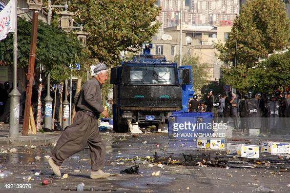 An Iraqi man crosses a street past security forces during clashes in Sulaimaniyah in Iraq's Kurdistan region on October 10 2015 Two demonstrators...