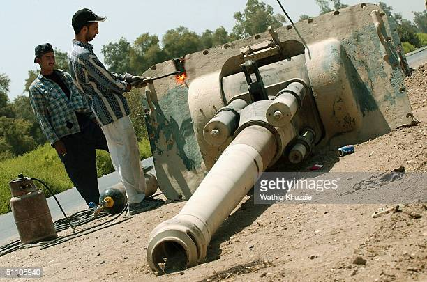 An Iraqi man cuts up an old Iraqi army weapon July 22 2004 in Mahaweel 43 miles south of Baghdad Iraq The metal from the weapons is transferred to...