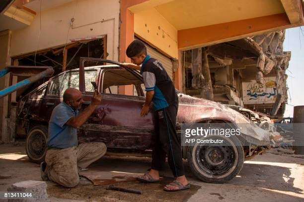 An Iraqi man fixes a car in west Mosul on July 12 2017 a few days after the government's announcement of the 'liberation' of the embattled city from...