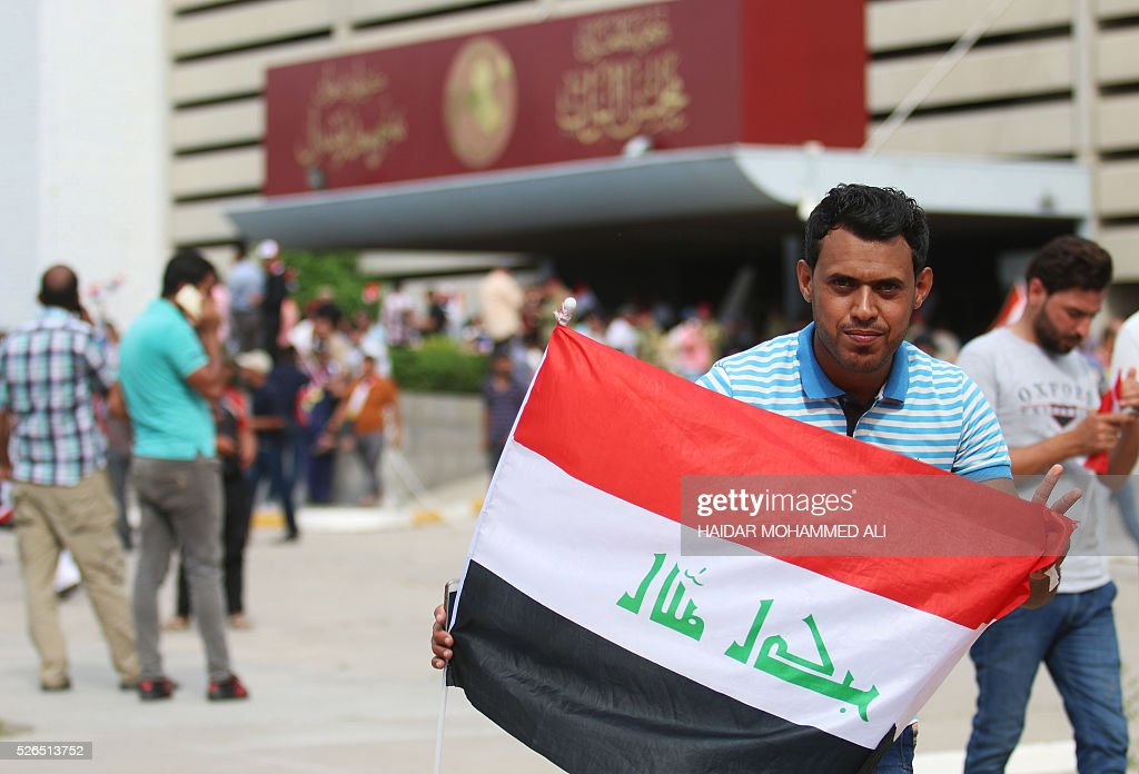 An Iraqi man holds a national flag as protesters gather outside the parliament after breaking into Baghdad's heavily fortified 'Green Zone' on April 30, 2016. Thousands of angry protesters broke into Baghdad's Green Zone and stormed the parliament building after lawmakers again failed to approve new ministers. Jubilant supporters of cleric Moqtada al-Sadr invaded the main session hall, shouting slogans glorifying their leader and claiming that they had rooted out corruption. / AFP / HAIDAR