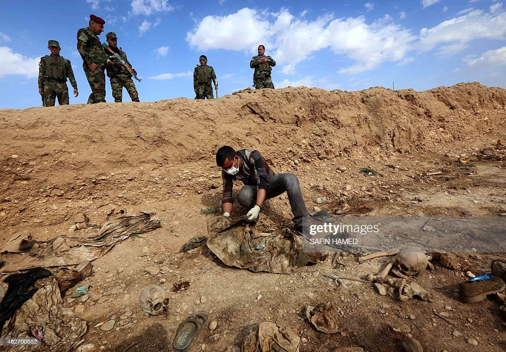 An Iraqi man inspects on February 3, 2015, the remains of members of the Yazidi minority killed by the Islamic State (IS) jihadist group after Kurdish forces discovered a mass grave near the village of Sinuni, in the northwestern Sinjar area. A peshmerga lieutenant colonel said the grave containing the remains of about 25 people was found during a search for explosives that IS often leaves behind, posing a threat to security forces and civilians even after they withdraw.