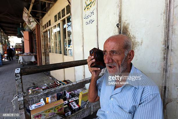 An Iraqi man listens on his portable radio to the speech of Iraqi Parliament Speaker Salim alJuburi in downtown Baghdad on August 11 as he delivers a...