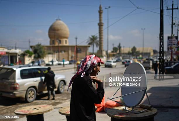 An Iraqi man looks at a satellite dish at a market in eastern Mosul on April 15 2017 Since Iraqi forces seized the east of Iraq's second city from...