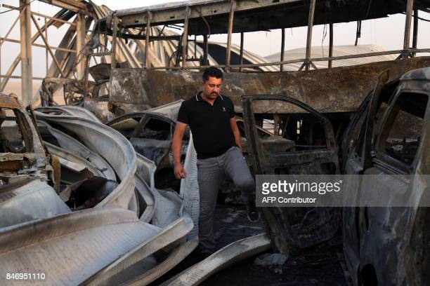 TOPSHOT An Iraqi man looks at the damage after gunmen and suicide car bombers killed dozens of people in two assaults claimed by Islamic State group...