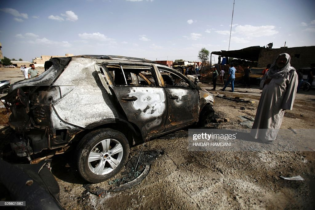 An Iraqi man looks at the damage following a twin suicide bombing attack, claimed by the Islamic State (IS) group in the southern Iraqi city of Samawah, situated deep in Iraq's Shiite heartland, on May 1, 2016. HAMDANI