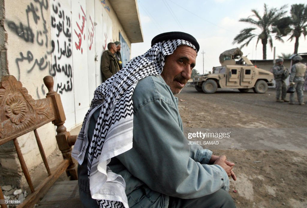 An Iraqi man looks on as US soldiers from the 6th Squadron, 8th Cavalry Regiment patrol a neighbourhood in southern Baghdad, 24 January 2008. A suicide bomber disguised as a policeman killed the provincial police chief for Iraq's main northern city of Mosul today as he visited the scene of an earlier blast in which 34 people died, police said. AFP PHOTO/Jewel SAMAD