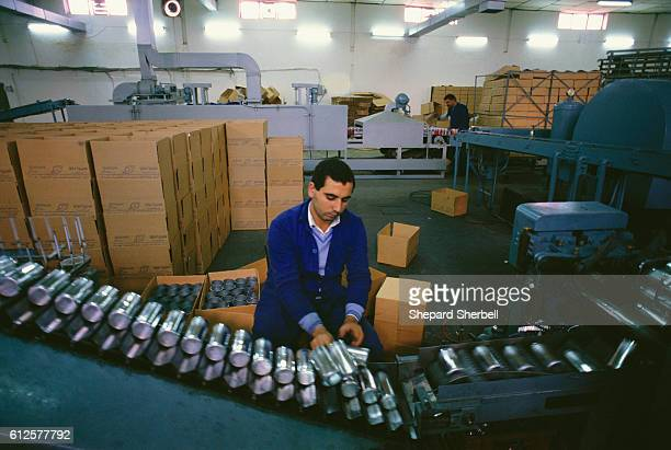 An Iraqi man makes Pepsi cans at a national can and plastic case works in Baghdad