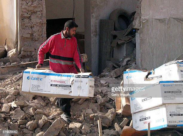 An Iraqi man moves posessions from his destroyed house on December 31 2004 in Fallujah Iraq Residents of the former rebel stronghold of Fallujah...