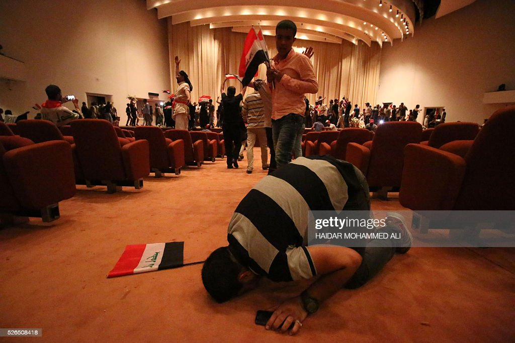 An Iraqi man prays as protesters gather inside the parliament after breaking into Baghdad's heavily fortified 'Green Zone' on April 30, 2016. A protest held outside the Green Zone escalated after parliament again failed to reach a quorum and approve new ministers to replace the current government of party-affiliated ministers. / AFP / HAIDAR
