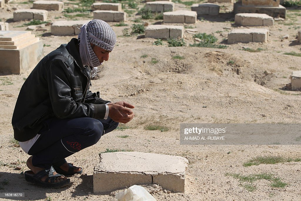 An Iraqi man prays on the tomb of an unknown person at a cemetery in the central city of Karbala on February 26, 2013, where the Iraqi government buried thousands of Iraqis who died in the sectarian war between Sunnis and Shiites between 2005 to 2008. Ten years after Saddam Hussein's overthrow, Iraqis are still searching for family and friends who went missing in the years of bloody sectarian conflict that swept the country after the dictator's fall. AFP PHOTO/AHMAD AL-RUBAYE