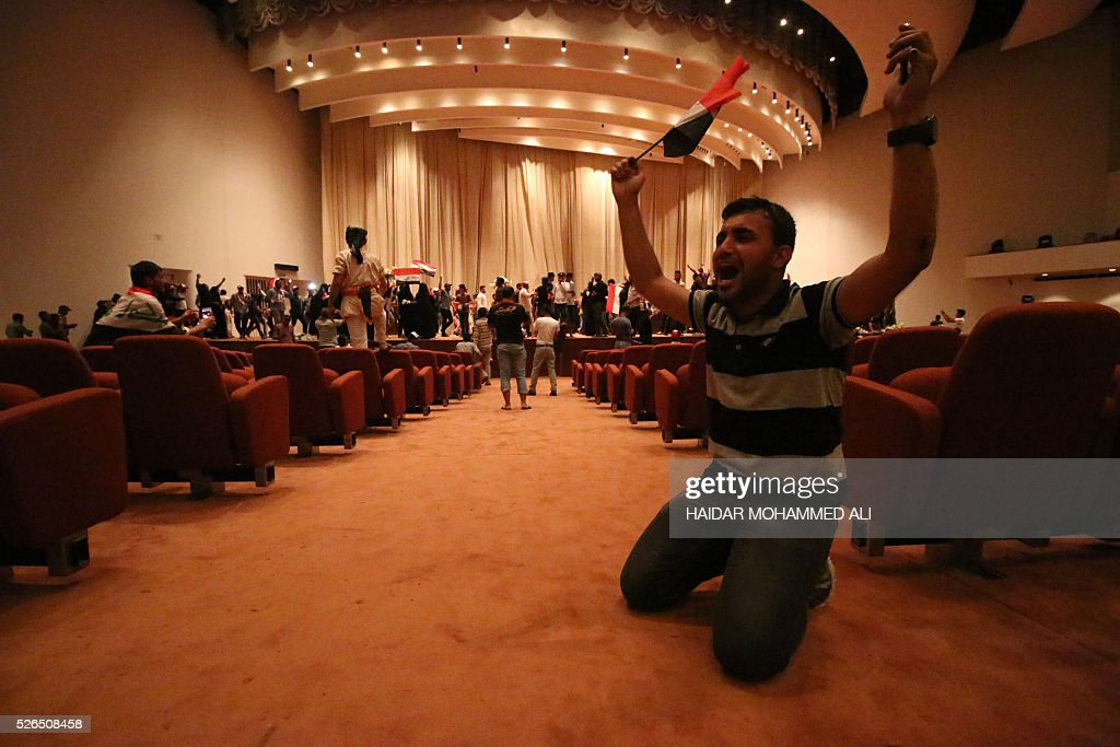 An Iraqi man reacts as protesters gather inside the parliament after breaking into Baghdad's heavily fortified 'Green Zone' on April 30, 2016. A protest held outside the Green Zone escalated after parliament again failed to reach a quorum and approve new ministers to replace the current government of party-affiliated ministers. / AFP / HAIDAR