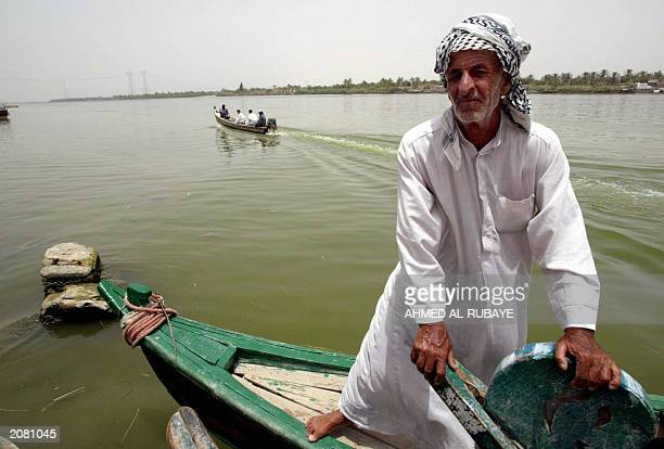 An Iraqi man readies to captain a small boat along the alFurat river 04 June 2003 in the southern city of Basra The boats are used to cross from one...