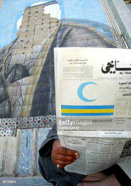 An Iraqi man reads a newspaper featuring a model of the new Iraqi flag in front of a disfigured mural of former Iraqi president Saddam Hussein 27...