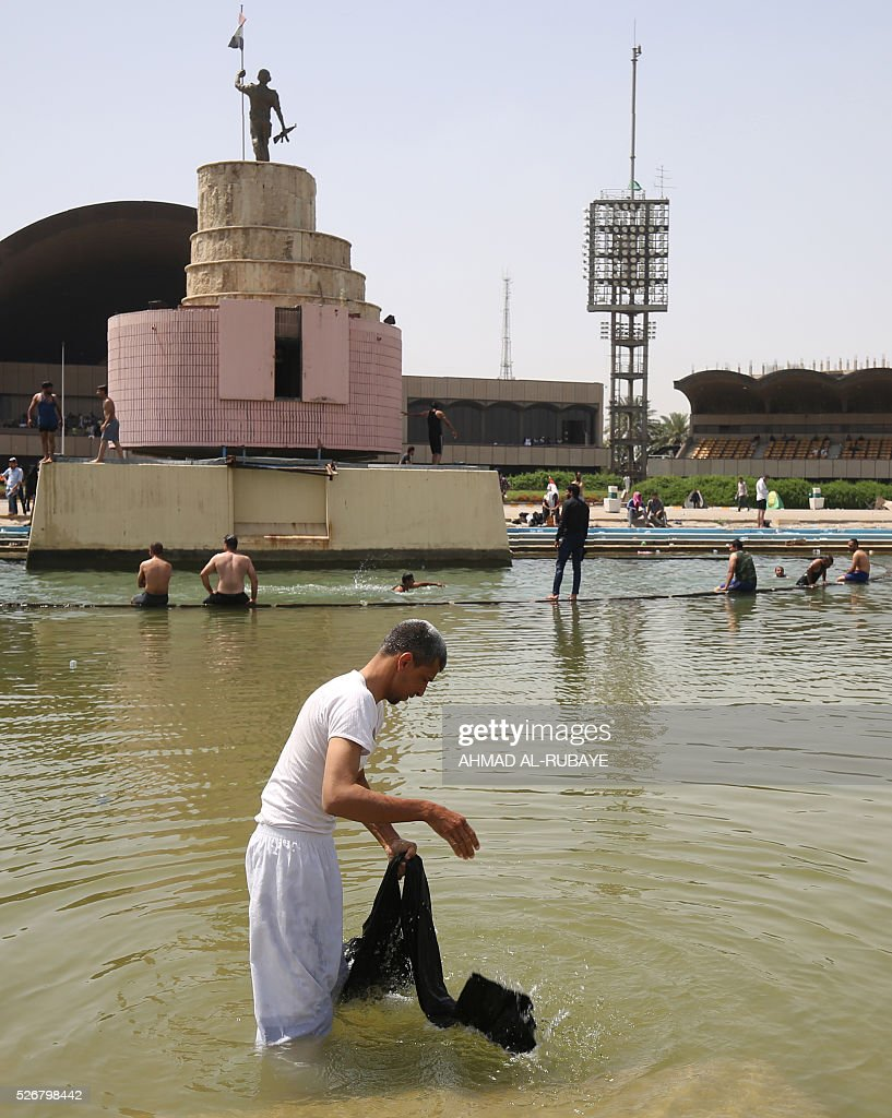 An Iraqi man refreshes himself in a pond in the parade grounds outside the parliament in Baghdad's heavily fortified 'Green Zone' on May 1, 2016, the day after supporters of Shiite cleric Moqtada al-Sadr broke into the area after lawmakers again failed to approve new ministers. Thousands of wide-eyed Iraqis marvelled at the fountains, flowers and perfect lawns in the capital's Green Zone, a day after protesters breached the walls of the fortified area. The visitors were mostly protesters who broke in but also included Baghdadis taking the opportunity to see an area that was off-limits for so many years that it acquired almost mythical status in the psyche of ordinary citizens RUBAYE