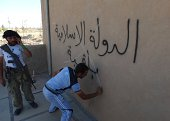 An Iraqi man scribbles on September 10 2014 over graffiti on the wall reading in Arabic 'the Islamic State is staying after Iraqi government forces...