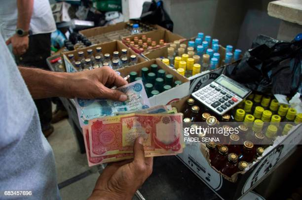 An Iraqi man sells alcohol at his shop in the embattled city Mosul on May 10 2017 Alcohol never completely disappeared from the city which for more...
