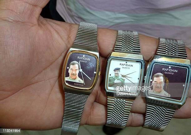 An Iraqi man sells watches bearing the picture of executed dictator Saddam Hussein to mark his birthday on April 28 2011 in Baghdad AFPPHOTO/SABAH...