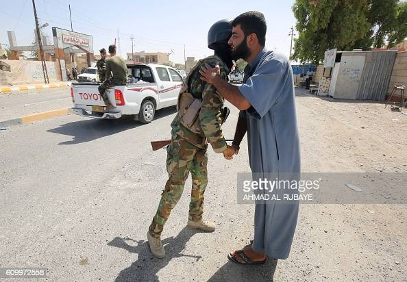 An Iraqi man shakes hands with a Sunni fighter from the popular mobilisation units supporting the government forces as they secure the town of...