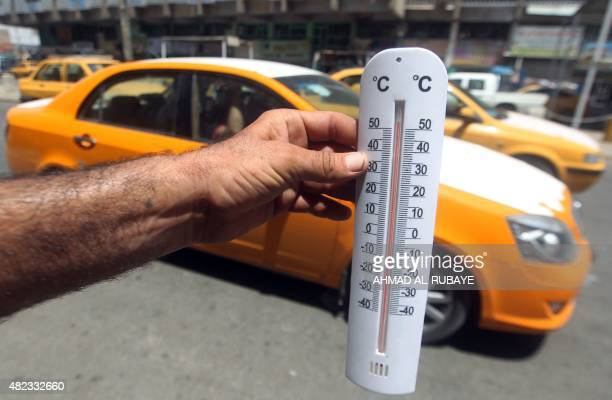 An Iraqi man shows a thermometer reading more than fifty degrees Celsius on July 30 2015 in the capital Baghdad AFP PHOTO / AHMAD ALRUBAYE