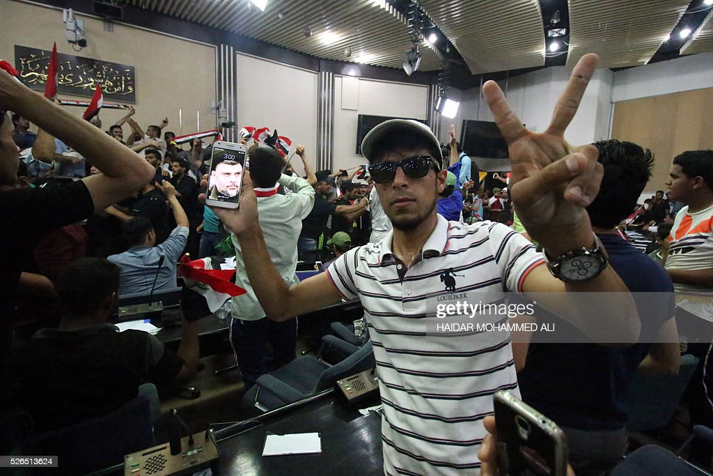 An Iraqi man shows on his smartphone a picture of Shiite cleric Moqtada al-Sadr as protesters gather inside the parliament after breaking into Baghdad's heavily fortified 'Green Zone' on April 30, 2016. Thousands of angry protesters broke into Baghdad's Green Zone and stormed the parliament building after lawmakers again failed to approve new ministers. Jubilant supporters of cleric Moqtada al-Sadr invaded the main session hall, shouting slogans glorifying their leader and claiming that they had rooted out corruption. / AFP / HAIDAR