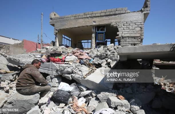 TOPSHOT An Iraqi man sits amid the rubble of destroyed houses in the Mosul alJadida area on March 26 following air strikes in which civilians have...