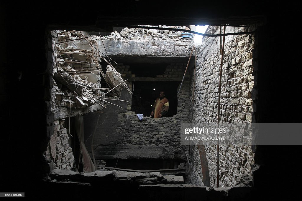 An Iraqi man stands in his house destroyed by a US air strike in 2008 as the US army was fighting radical Shiite cleric Muqtada al-Sadr's Mahdi militia in Baghdad's Sadr City on December 10, 2012. A US-led coalition invaded Iraq in 2003, toppling dictator Saddam Hussein and beginning a conflict that cost the lives of tens of thousands of Iraqis, thousands of Americans and hundreds of billions of dollars. Almost 10 years later and after that the last convoy of American armoured vehicles rolled across the border into Kuwait on the chilly morning of December 18, 2011, many Iraqis still lack basic services such as consistent electricity and clean water, and though levels of violence are down, insurgents continue to carry out bombings and shootings almost every day. AFP PHOTO/AHMAD AL-RUBAYE