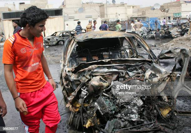 An Iraqi man stands near a car damaged in a car bomb explosion in Sadr city on April 23 2010 in Baghdad Iraq A series of bombings rocked a market and...