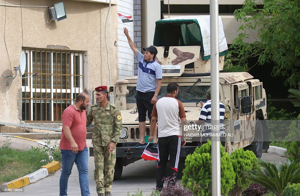 An Iraqi man stands on a military vehicle and holds a national flag as protesters gather outside the parliament after breaking into Baghdad's heavily fortified 'Green Zone' on April 30, 2016. Thousands of angry protesters broke into Baghdad's Green Zone and stormed the parliament building after lawmakers again failed to approve new ministers. Jubilant supporters of cleric Moqtada al-Sadr invaded the main session hall, shouting slogans glorifying their leader and claiming that they had rooted out corruption. / AFP / HAIDAR