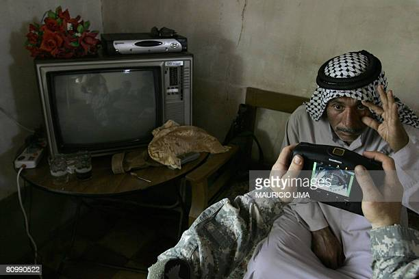 An Iraqi man stretches his eye as a US soldier scans his iris using a biometrics digital system camera during an enlistment program session to join...
