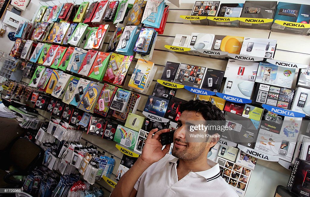 An Iraqi man uses a mobile phone at a store on June 26, 2008 in Baghdad, Iraq. The war-damaged aging landline telephone infrastructure means Iraqis are increasingly more dependent on mobile phones in daily life and business.