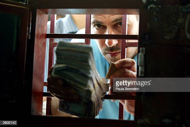 An Iraqi man waits at the bank window to exchange his old dinar for the new Iraqi dinar at the Bank of Baghdad October 15 2003 in Baghdad Iraq as the...