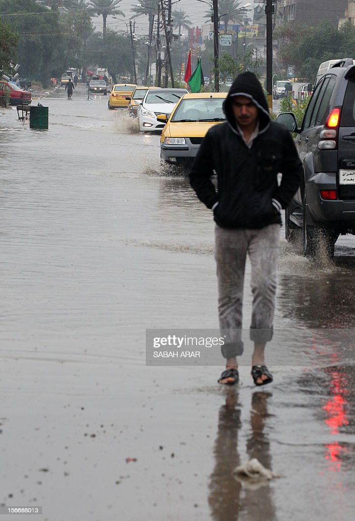 An Iraqi man walks near cars driving in water-logged roads after continuous overnight rainfall inundated many of Baghdad's main streets on November 19, 2012, causing problems with the capitals sewage system.