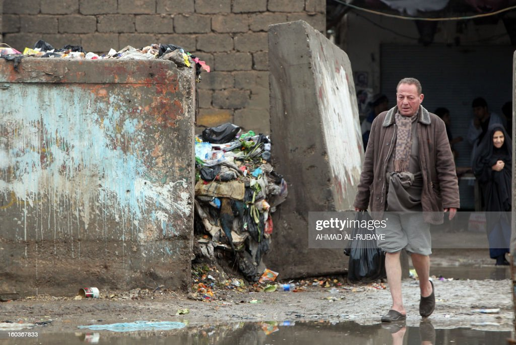 An Iraqi man walks past a garbage dump on the outskirts of Baghdad's impoverished district of Sadr City, January 30, 2013. Around a quarter of Iraq's population are estimated by the country's Planning Ministry to live in poverty, and many survive in vast refuge dumps where they search for subsistence, either via using disposed goods or finding items that can be handed to recycling plants for money.