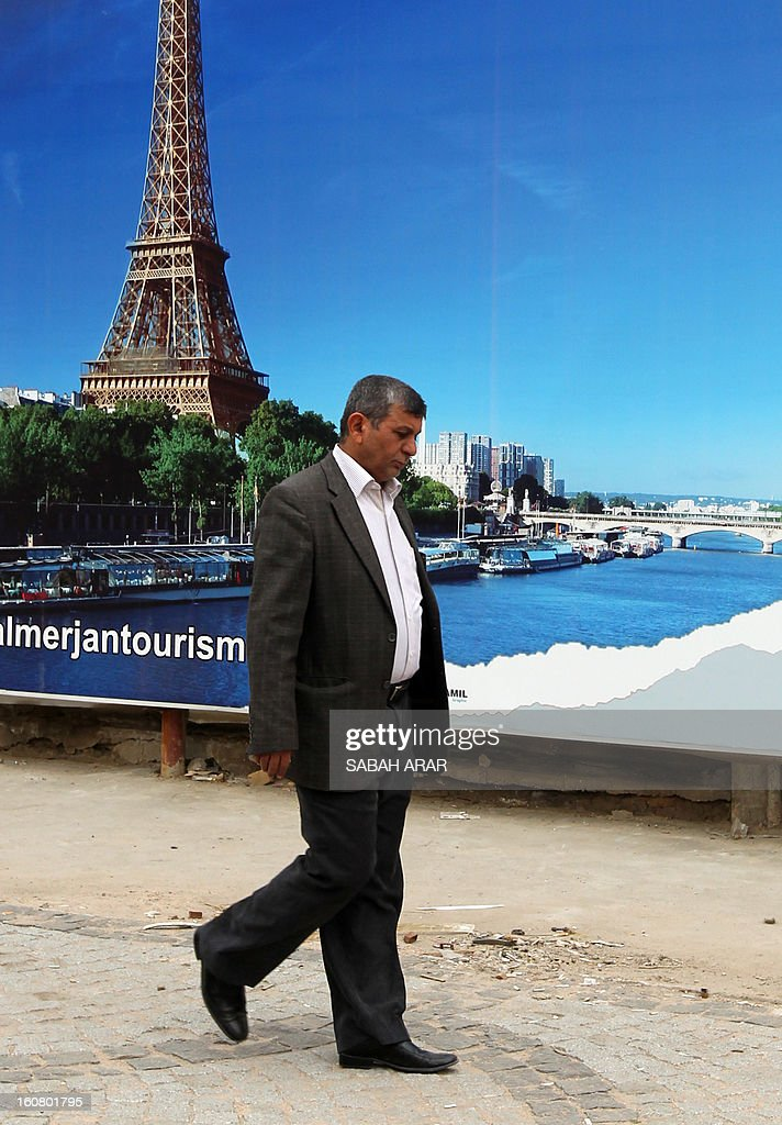 An Iraqi man walks past a giant advert making the promotion of a travel agency organizing trips to Paris, a new destination for the country, on February 6, 2013 in the Iraqi capital, Baghdad. Iraqis are now allowed to ask for European visas.