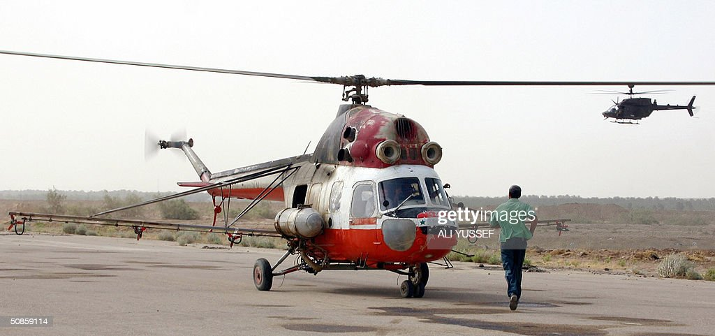An Iraqi man walks towards a Russian-made MI-2 Iraqi helicopter before taking off to begin crop-dusting the date palm fields in the city of Baquba, northeast of Baghdad 20 May 2004. Iraqi pilots are flying again for the first time since the war started over a year ago, to spray date palm fields in a joint operation with coalition forces in eastern Iraq.