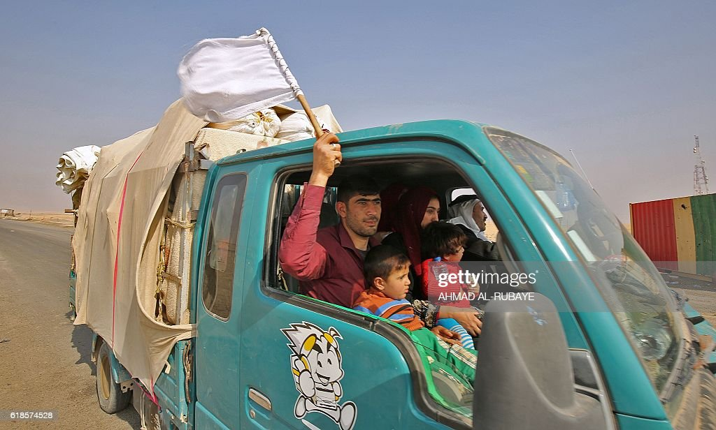 TOPSHOT - An Iraqi man waving a white flag sits with his family in a vehicle driving near Sin al-Dhuban village, some 40 kilomtres south of Mosul, after they fled the Hammam al-Alil area on October 27, 2016, as government forces take part in an operation to retake the main hub city from the Islamic State (IS) group jihadists. The United States said that up to 900 Islamic State group jihadists have been killed in the offensive to retake Iraq's Mosul, as camps around the city filled with fleeing civilians. RUBAYE