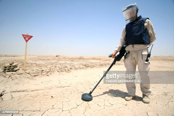 An Iraqi man wearing protective gear searches for landmines in the Shalamja border crossing west of Basra on the border between Iraq and Iran on June...