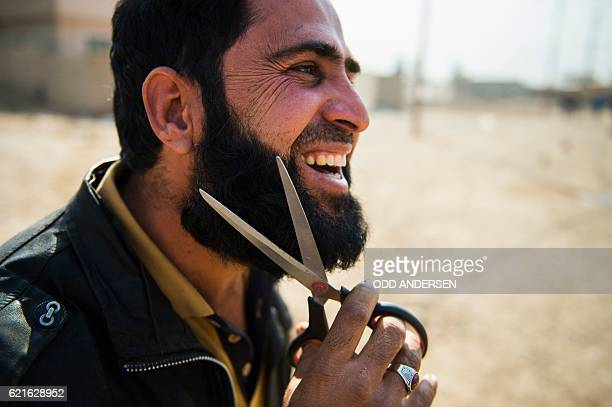 TOPSHOT An Iraqi man who fled the fighting uses a pair of scissors to trim his beard after reaching the Iraqi army 9th armoured division base...