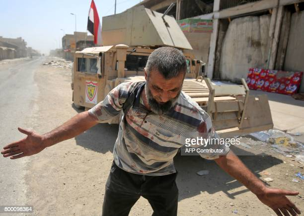 TOPSHOT An Iraqi man who was injured in a suicide attack as people were escaping the Old City of Mosul reacts as he arrives at a makeshift hospital...